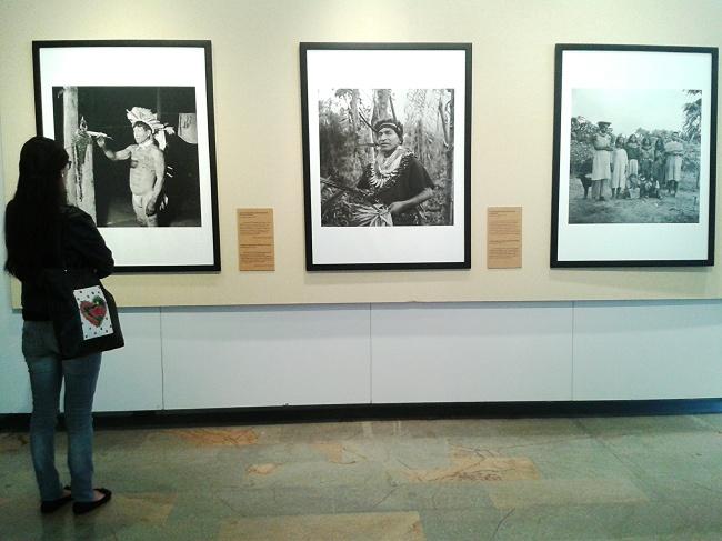 Mujer mira los  cuadros de chamanes indígenas